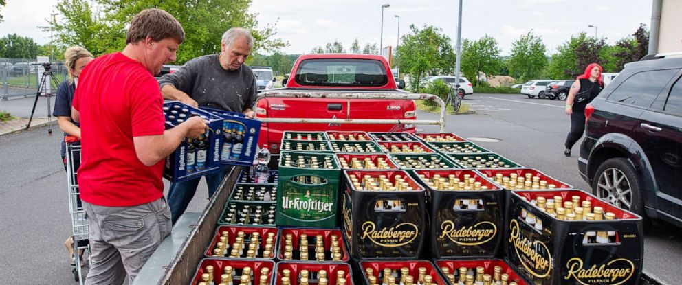 PHOTO: A woman and two men load beer crates near a local supermarket onto a trailer in Saxony, Ostritz, Germany, June 22, 2019.