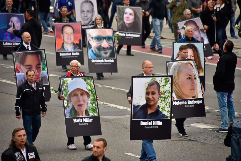 PHOTO: Demonstrators hold up placards showing portraits of victims of refugees during a protest organised by the far-right Alternative for Germany (AfD) party, on Sept. 1, 2018 in Chemnitz, Germany.