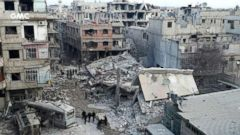 'PHOTO: Syrians gather between destroyed buildings after an attack of airstrikes and shelling by Syrian government forces, in Ghouta, a suburb of Damascus, Syria, Feb. 22, 2018.' from the web at 'https://s.abcnews.com/images/International/ghouta-syria-1-ap-jt-180224_16x9t_240.jpg'