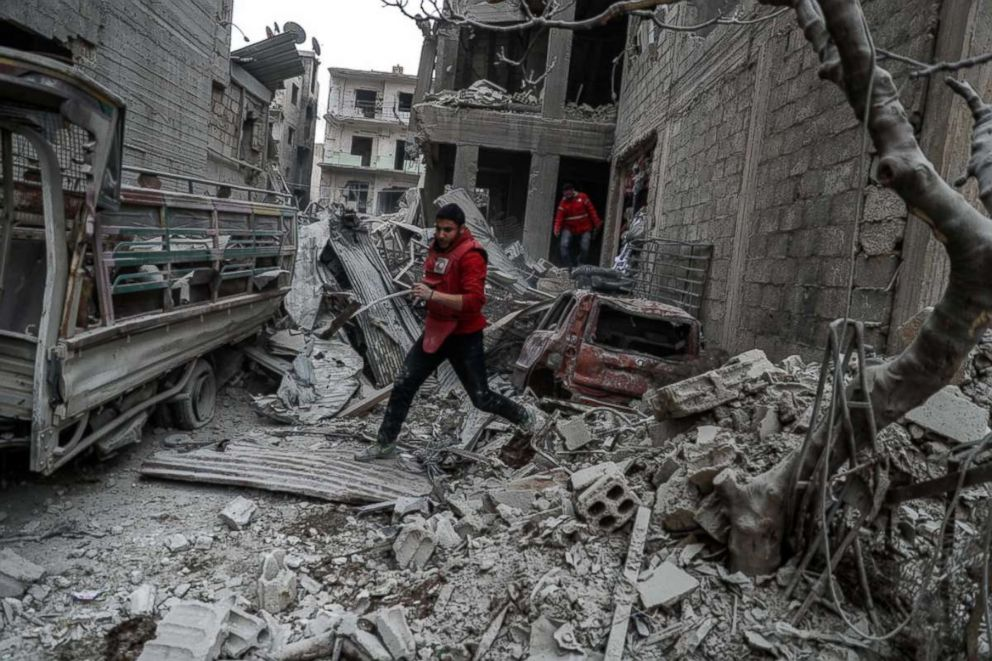 PHOTO: A red crescent volunteer runs after a bombing, in rebel-held Douma, Eastern Ghouta, Syria, Feb. 22, 2018. More than 25 people were killed in Douma after several airstrikes and shelling by forces allegedly loyal to the Syrian Government.