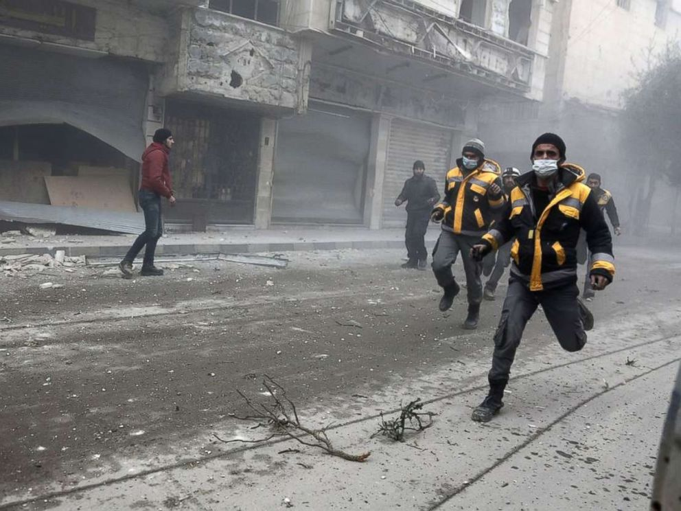 PHOTO: Syrian rescuers and civilians run at the site of Syrian government bombardments in Hamouria, in the besieged Eastern Ghouta region on the outskirts of the capital Damascus on Feb. 22, 2018.