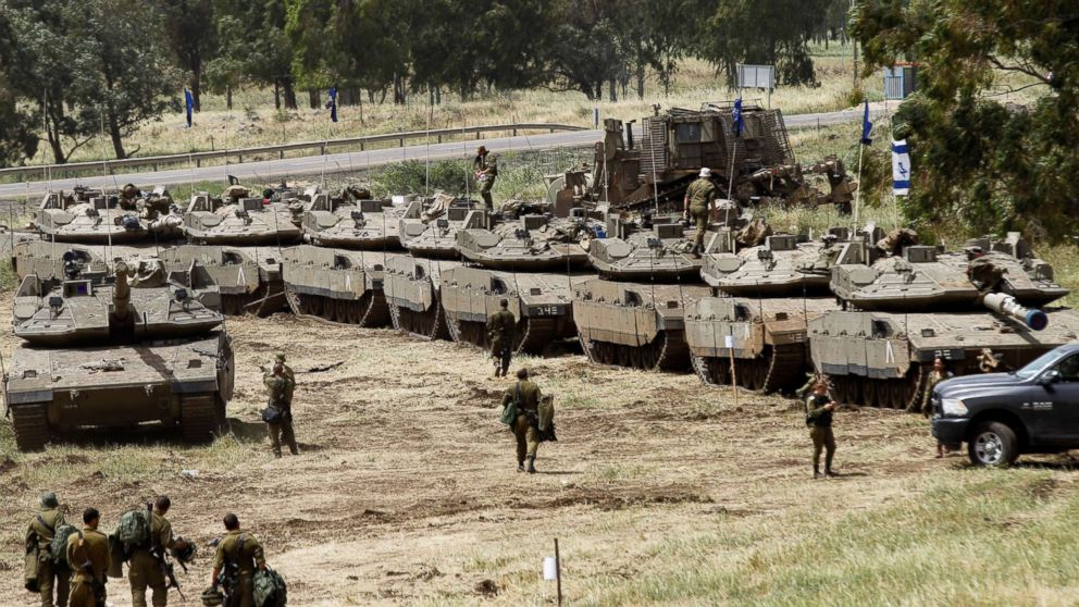 Israeli soldiers pass Merkava Mark IV tanks during a battle Military drilling in the Golan Heights, annexed by the Israelis on May 1, 2018.