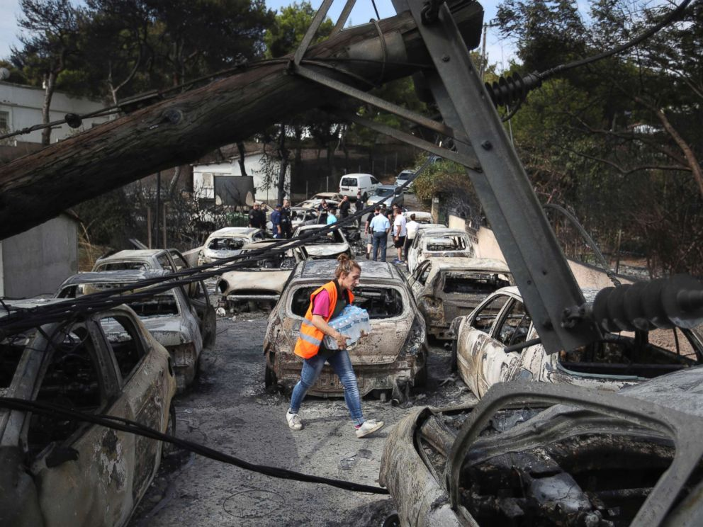 PHOTO: A woman carries bottles of water as people stand amid the charred remains of burned-out cars in Mati east of Athens, July 24, 2018.