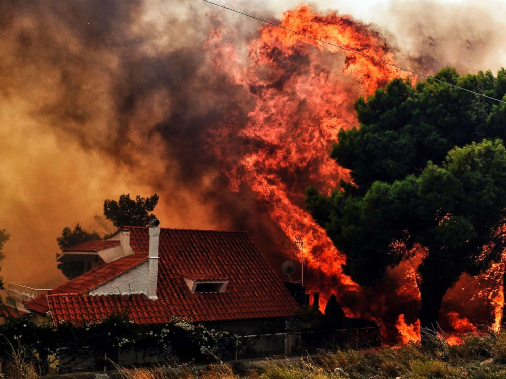 PHOTO: A house is threatened by a huge blaze during a wildfire in Kineta, near Athens, on July 23, 2018.