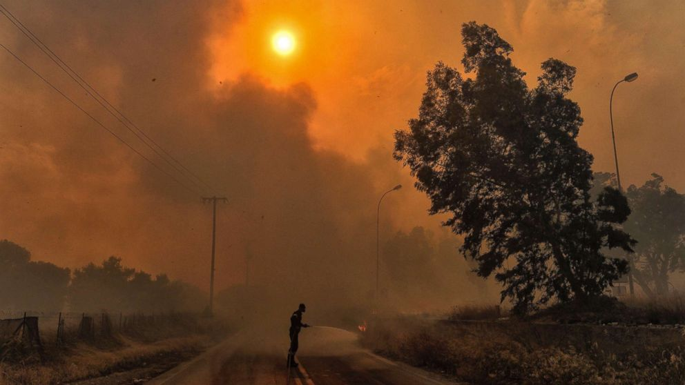 A firefighter tries to extinguish hotspots during a wildfire in Kineta, near Athens, July 23, 2018.
