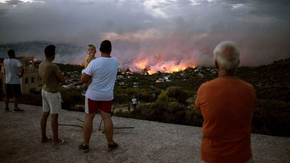 People watch a wildfire in the town of Rafina, near Athens, Greece, July 23, 2018.