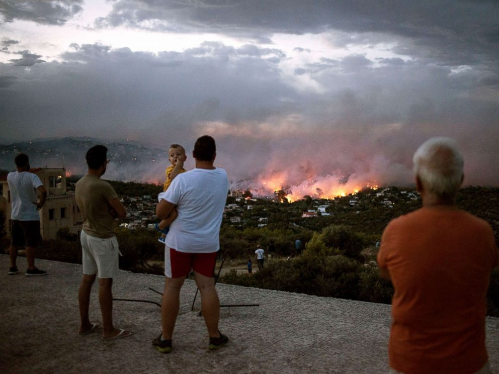 PHOTO: People watch a wildfire in the town of Rafina, near Athens, Greece, July 23, 2018.