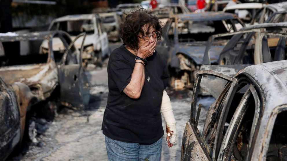 A woman reacts as she tries to find her dog, following a wildfire at the village of Mati, near Athens, Greece, July 24, 2018.