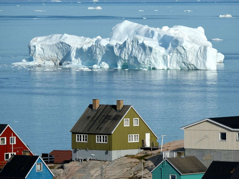 PHOTO: An iceberg floats in Disko Bay behind houses during unseasonably warm weather, July 30, 2019, in Ilulissat, Greenland.