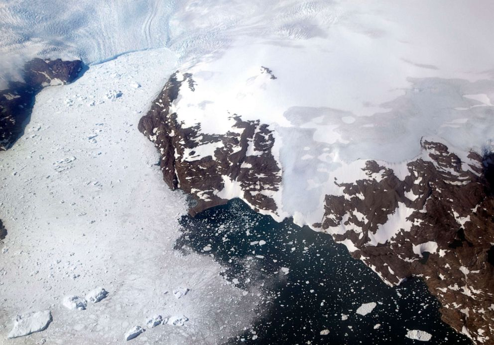 PHOTO: In this file photo dated Thursday, Aug. 3, 2017, a glacier at left calves icebergs into a fjord off the Greenland ice sheet in southeastern Greenland.