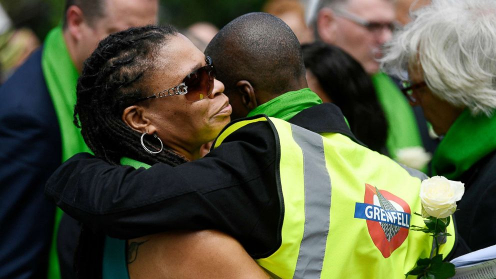 Friends and relatives of victims of the Grenfell fire react before taking part in a silent procession, in tribute to victims as they mark one year anniversary of the fire in London, June 14, 2018.