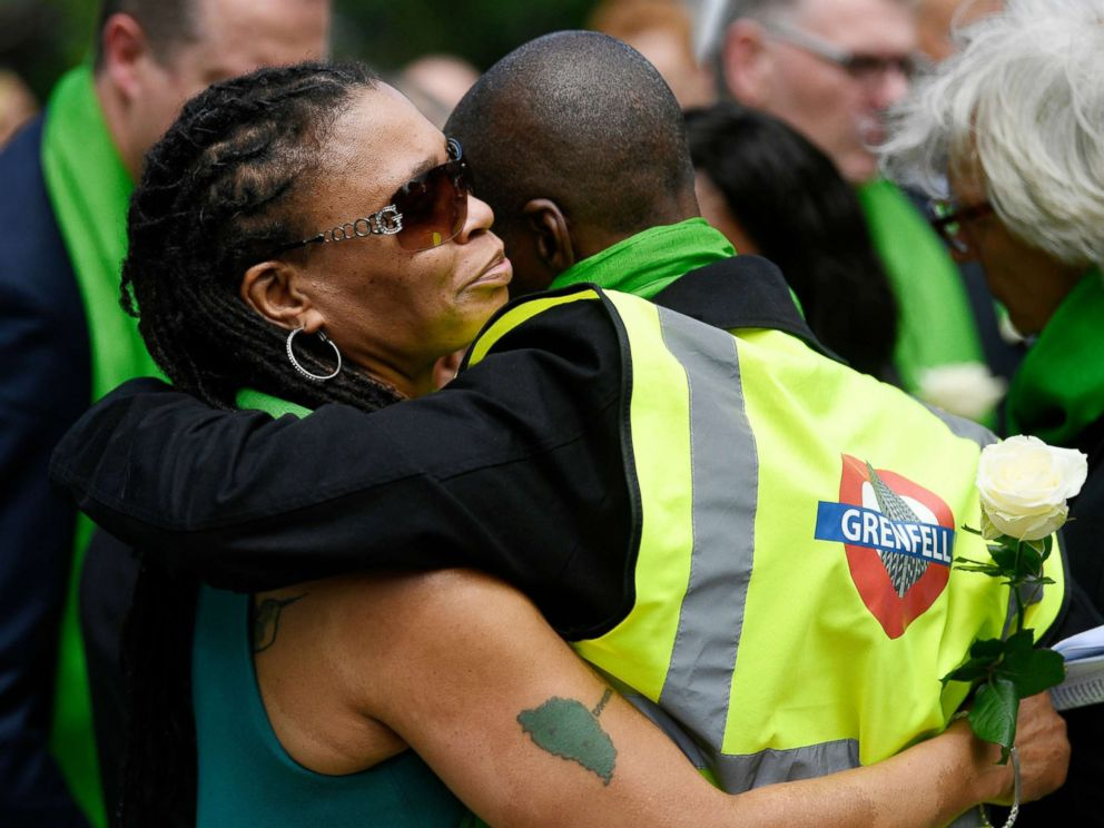 PHOTO: Friends and relatives of victims of the Grenfell fire react before taking part in a silent procession, in tribute to victims as they mark one year anniversary of the fire in London, June 14, 2018.