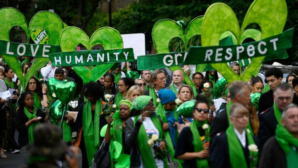 Friends and relatives of victims of the Grenfell fire wear symbolic green, as they take part in a silent procession to mark the one year anniversary of the fire in London, June 14, 2018.