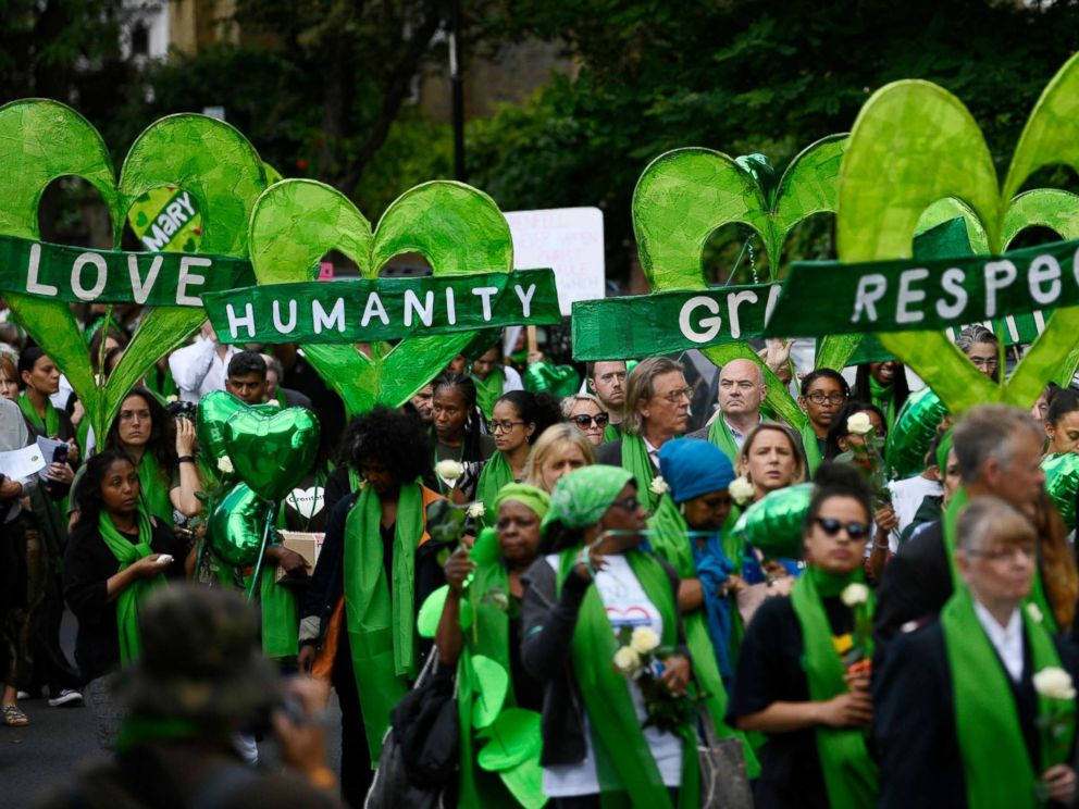 PHOTO: Friends and relatives of victims of the Grenfell fire wear symbolic green, as they take part in a silent procession to mark the one year anniversary of the fire in London, June 14, 2018.