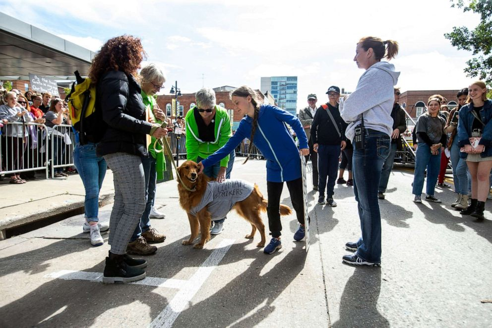 PHOTO: Climate activist Greta Thunberg pets Cleo the Climate Dog, a golden-retriever, before speaking to reporters after the Town-Gown Climate Accord hosted by the Iowa City Climate Strikers, Oct., 4, 2019, in Iowa City, Iowa.
