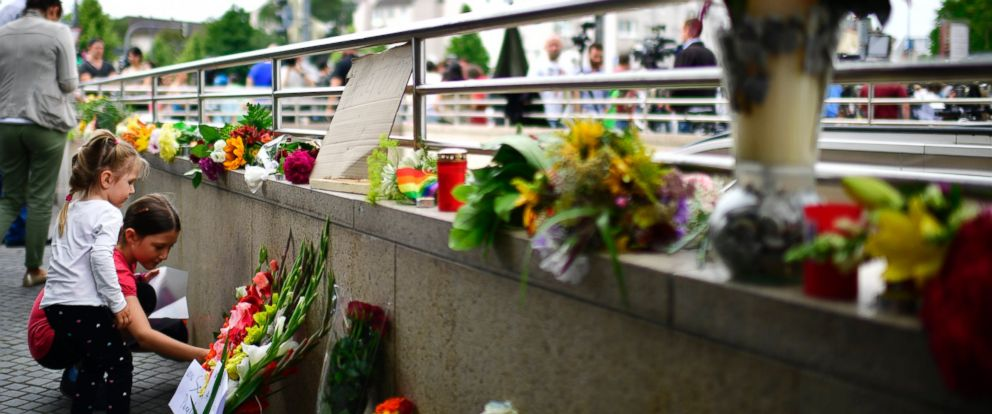 PHOTO: MUNICH, GERMANY - JULY 23: Two girls lay down flowers and candles outside the OEZ shopping center the day after a shooting spree left nine victims dead on July 23, 2016 in Munich, Germany.