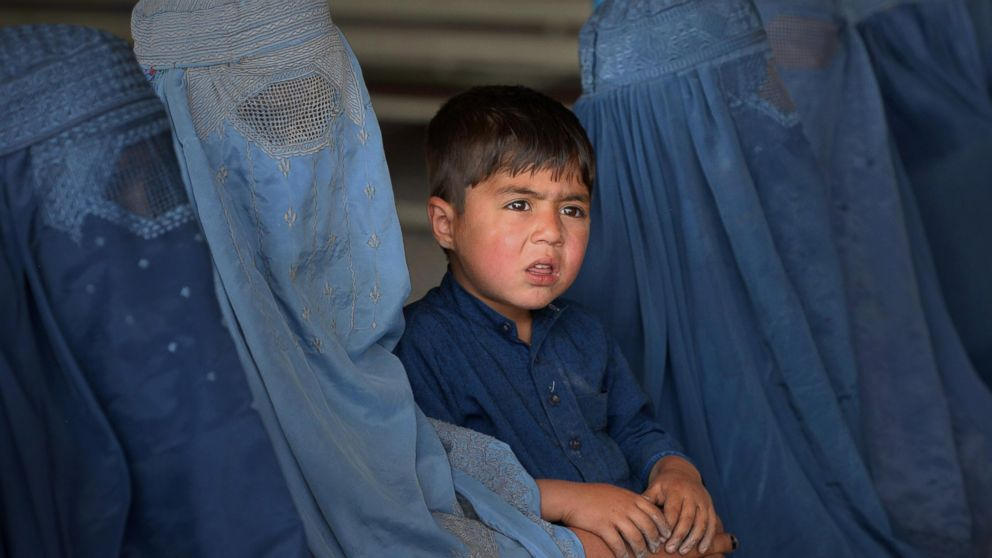 Afghan refugee families wait to be registered at the United Nations High Commissioner for Refugees (UNHCR) repatriation center on the outskirts of Peshawar, April 27, 2017, as they prepare to return to their home country after fleeing civil war and Taliban rule.