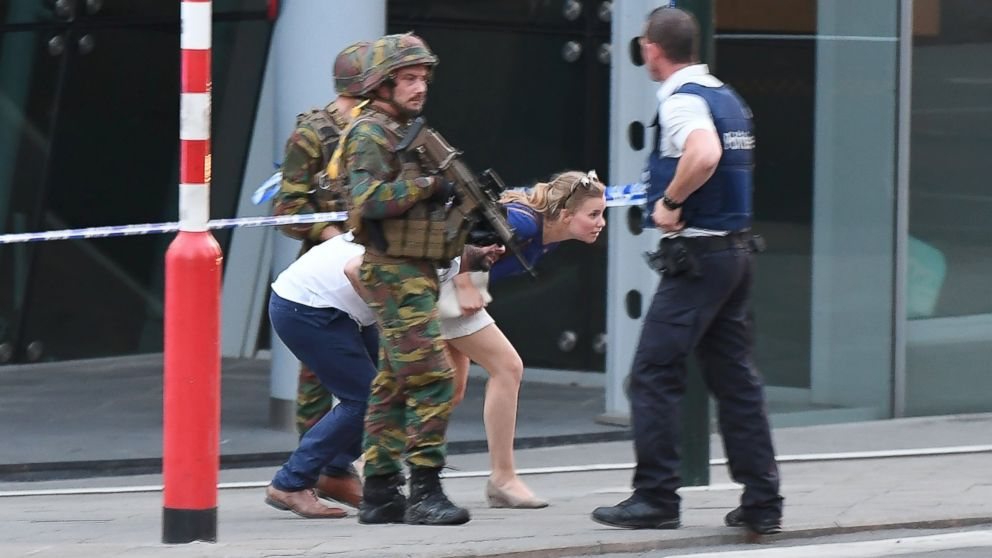 Soldiers and police officials guide members of the public on a street outside Gare Centrale in Brussels on June 20, 2017, after an explosion in the Belgian capital.