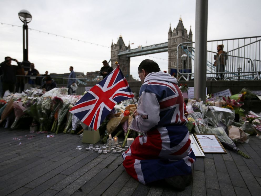 PHOTO: A man holds a Union flag as he kneels near flowers laid at Potters Fields Park in London, June 5, 2017, during a vigil to commemorate the victims of the terror attack on London Bridge.