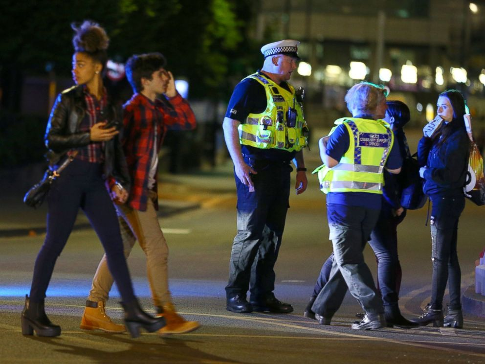 PHOTO: People walk past police near the Manchester Arena on May 23, 2017 in Manchester, England.