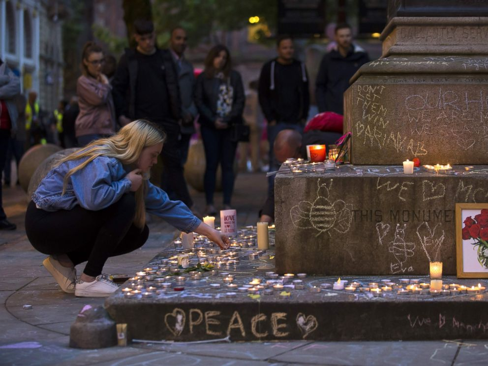 PHOTO: A member of the public lights memorial candles before a vigil in St Anns Square in Manchester, north west England on May 29, 2017, placed in tribute to the victims of the May 22 terror attack at the Manchester Arena.