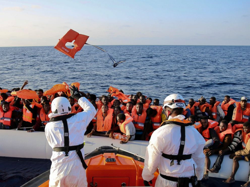 PHOTO: Safety jackets are thrown to migrants on a rubber dinghy from the vessel Responder, run by the Malta-based NGO Migrant Offshore Aid Station (MOAS) and the Italian Red Cross.