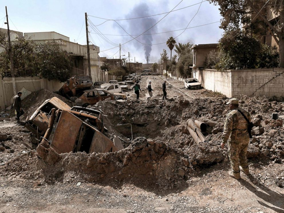 PHOTO: A member of the Iraqi military looks at a crater made by an air strike in west Mosul as Iraqi troops continue battling against Islamic State fighters to further advance inside the city, on March 7, 2017.