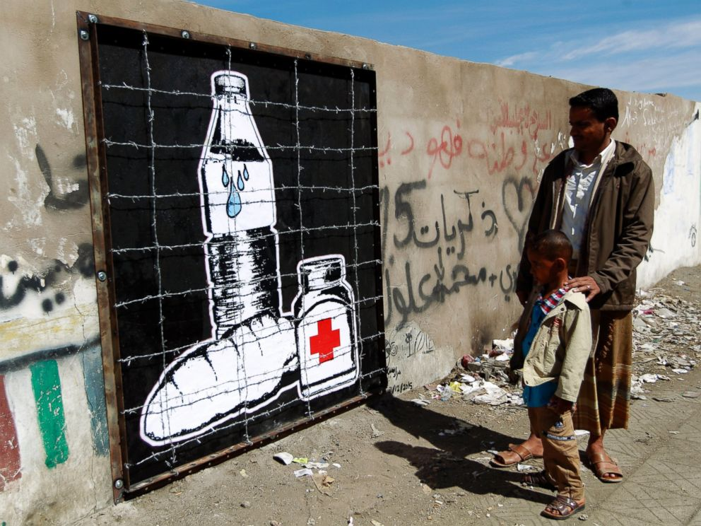 PHOTO: Yemenis look at a piece of art by Murad Subay depicting the blockade in Yemen and the prevention of the entry of food and medicine due to the military campaign against Iran-backed rebels, in Sanaa, Yemen, Dec. 31, 2015.