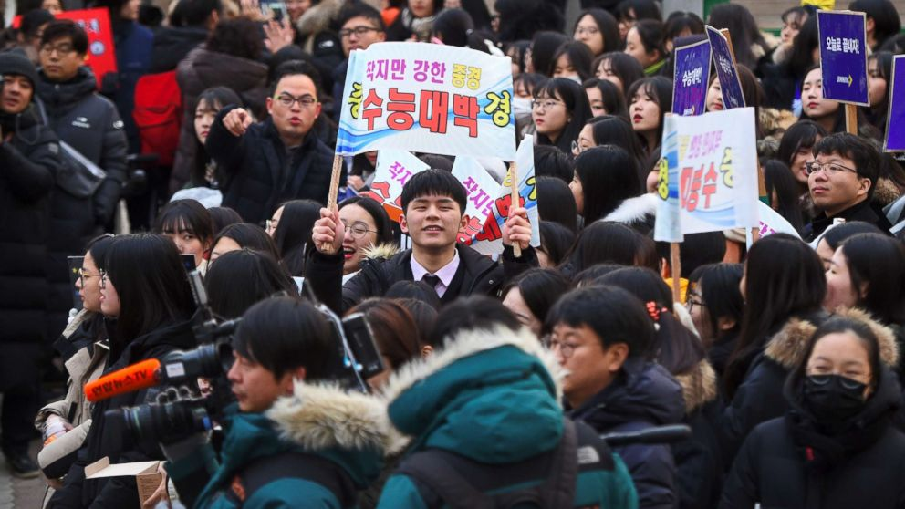 High school students cheer their seniors taking the annual College Scholastic Ability Test, a standardized exam for college entrance, at a high school in Seoul on November 23, 2017.