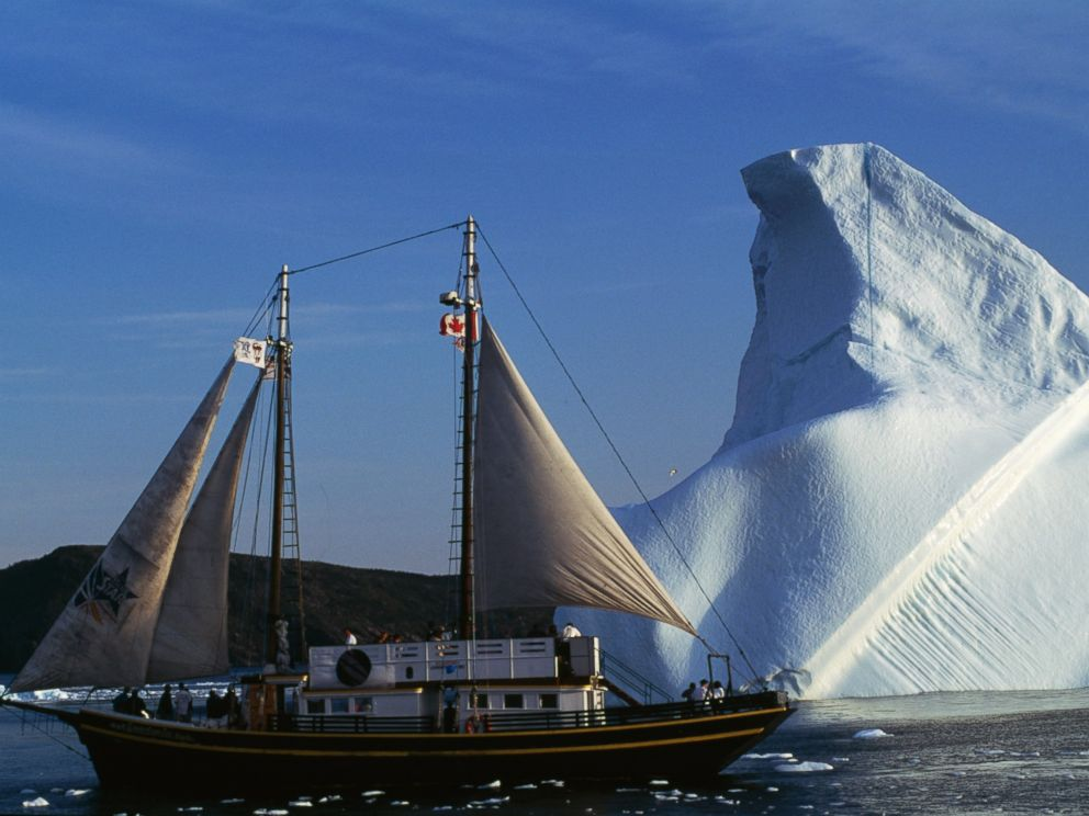 PHOTO: A Sailboat in front of an iceberg, in Saint Bay, Newfoundland, Canada.