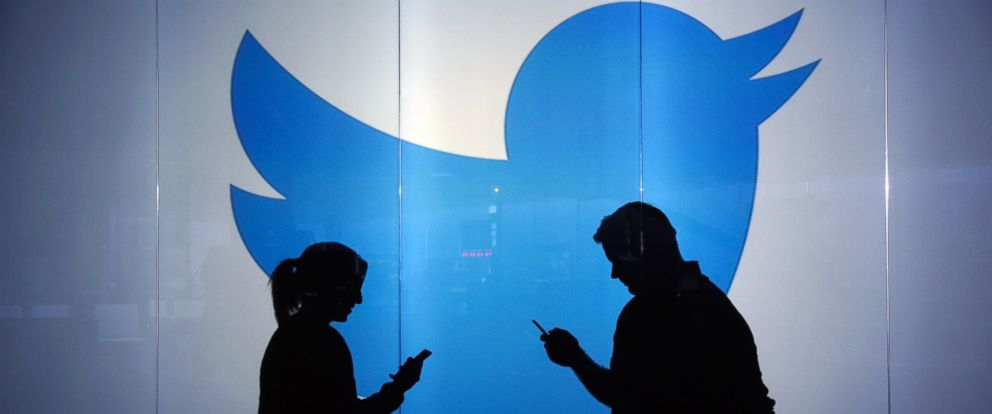 PHOTO: People stand in front of a Twitter logo in a stock photo, Jan. 5, 2016.