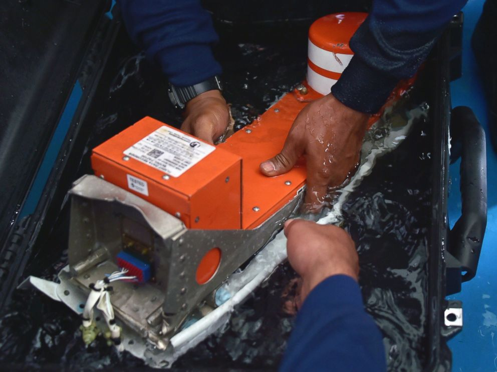 PHOTO: Indonesian divers onboard the Indonesian navy vessel KRI Banda Aceh handle the Flight Data Recorder of the AirAsia flight QZ8501 after it was retrieved from the Java Sea on Jan. 12, 2015.
