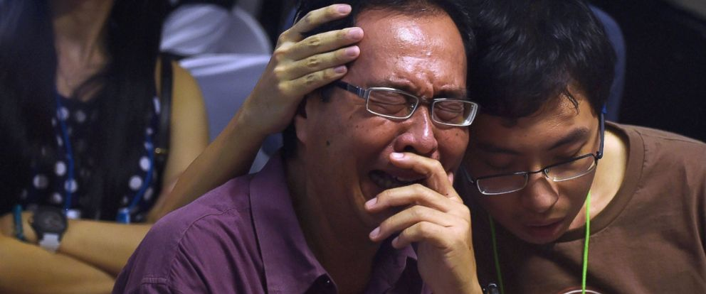 PHOTO: Family members of passengers aboard AirAsia flight QZ8501 react after watching news reports inside the crisis center set up at Juanda International Airport in Surabaya, Indonesia on Dec. 30, 2014.