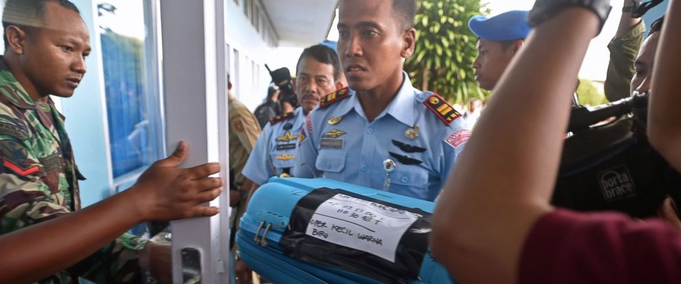 PHOTO: A member of the Indonesian air force carries an item retrieved from the Java sea during search and rescue operations for the missing AirAsia flight QZ8501, in Pangkalan Bun, Central Kalimantan, Dec. 30, 2014.