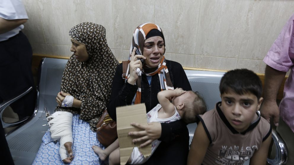 Palestinian patients sit in a hallway of the Al-Aqsa Martyrs hospital in Deir al-Balah in the Gaza Strip after the building was hit by an Israeli army shelling on July 21, 2014.