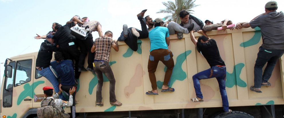 PHOTO: Iraqi men who volunteered to join the fight against a major offensive by jihadists in northern Iraq climb on an army truck outside a recruiting center in the capital Baghdad on June 13, 2014.