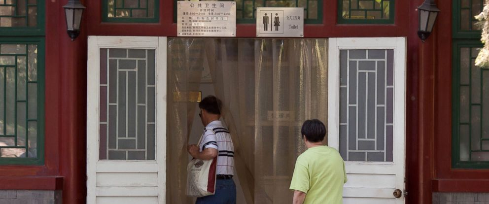 PHOTO: Men walk into a public toilet in Beijing, China on May 24, 2012.