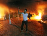 PHOTO: An armed man waves his rifle as buildings and cars are engulfed in flames after being set on fire inside the US consulate compound in Benghazi, Libya, Sept. 11, 2012.