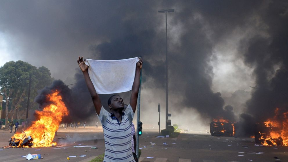 A protester holds a white cloth as cars and documents burn outside the parliament in Ouagadougou, Burkina Faso, Oct. 30, 2014.