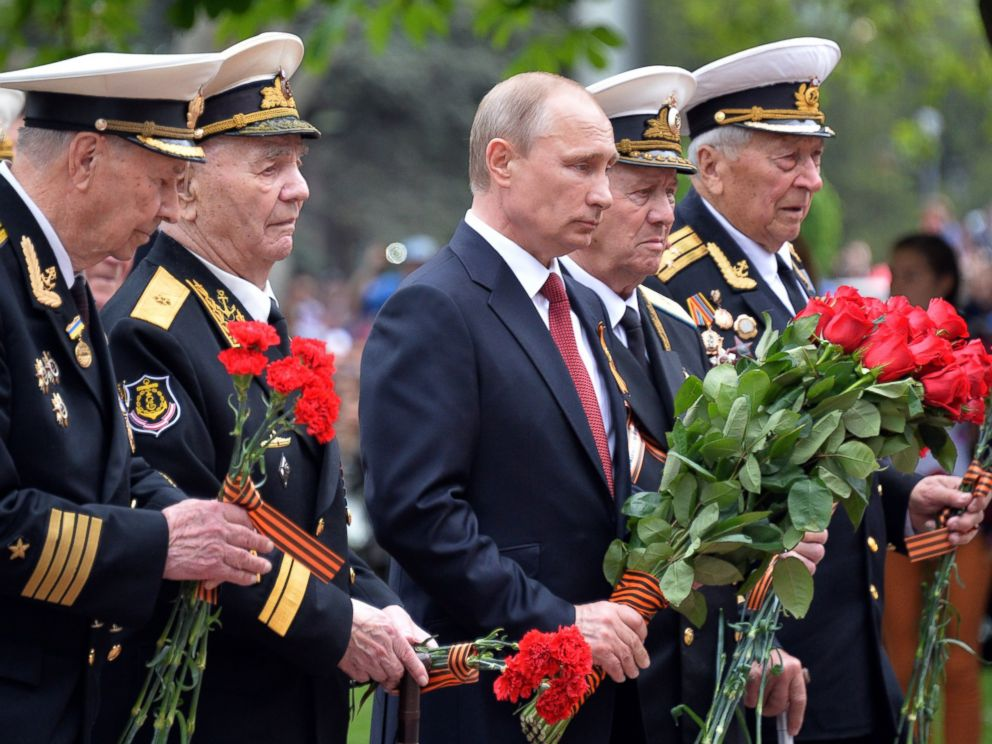 PHOTO: Russias President Vladimir Putin, center, and World War II veterans law flowers at a war memorial during their visit to the Crimean port of Sevastopo, May 9, 2014.