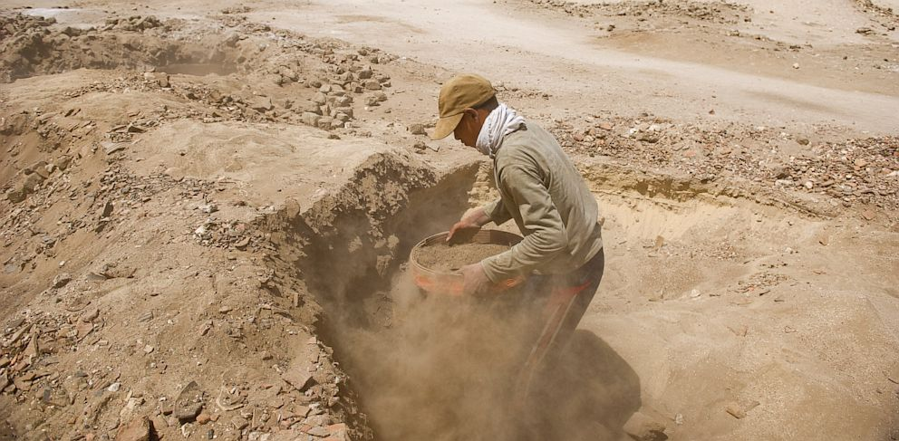 PHOTO: Looters dig through the sand, sifting and unearthing Roman and Pharaonic antiquities to sell on June 26, 2013 in Sheikh Ibada, Egypt.