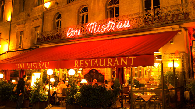 PHOTO: Lou Mistrau restaurant illuminated at night on Place de lHorloge, Avignon, France.