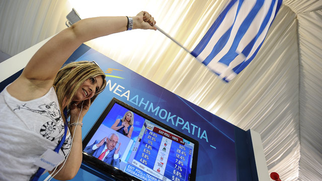 PHOTO: New Democracy (ND) party supporters celebrate as they watch the exit polls at the partys main election campaign kiosk in Athens on June 17, 2012.