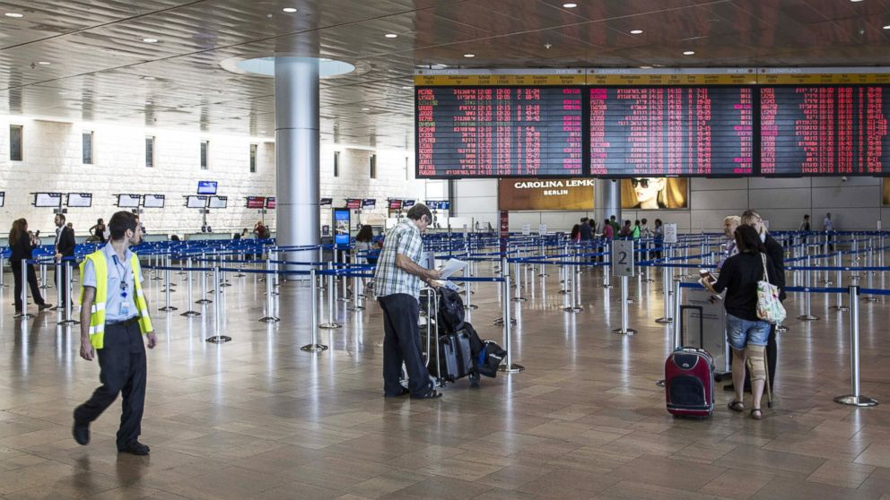 Israeli passengers walk near a departure time flight board displaying various cancellations at Ben Gurion International airport, near Tel Aviv, on July 23, 2014.