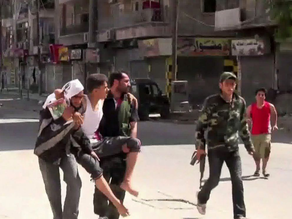 PHOTO: An image grab taken from AFP TV on August 5, 2012 shows Syrian rebels carrying a wounded man in the Salaheddin district of the northern Syrian city of Aleppo on Aug. 3, 2012.