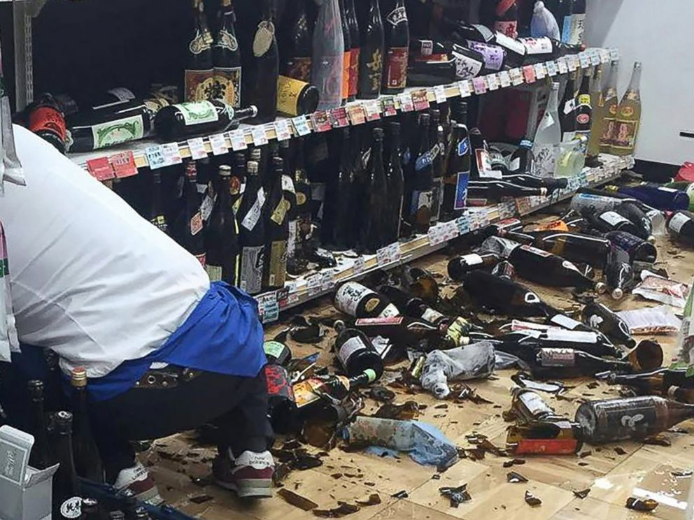 PHOTO: A shop clerk cleans broken wine bottles following an earthquake in Kumamoto, Japan on April 14, 2016.
