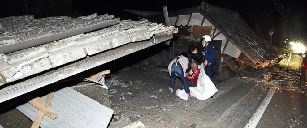 PHOTO: Local residents sit in front of their collapsed house after an earthquake jolted the area on April 14, 2016 in Mashiki, Kumamoto, Japan.