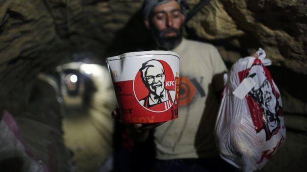 PHOTO: A smuggler carries food from Kentucky Fried Chicken to be delivered through an underground tunnel linking the Gaza Strip to Egypt, on May 13, 2013 in Rafah, Gaza.