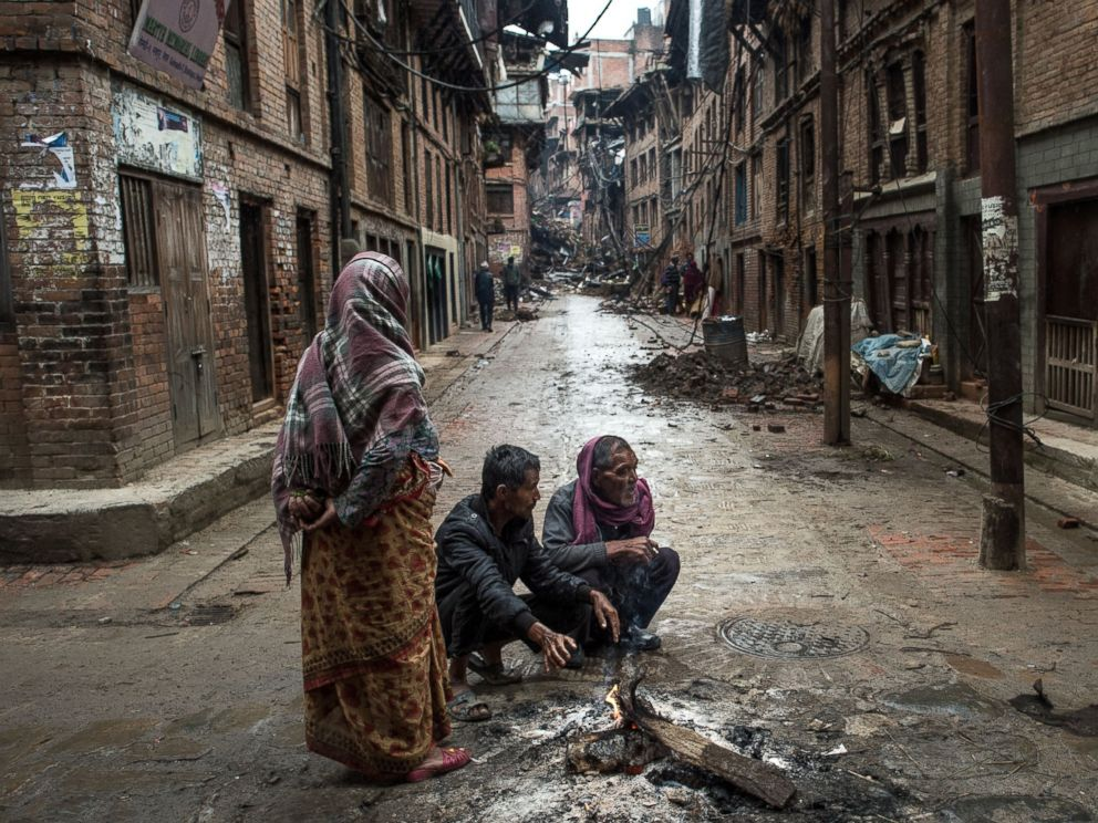 PHOTO: Local residents warm themselves by a fire in the street in Bhaktapur on April 30, 2015 in Kathmandu, Nepal.