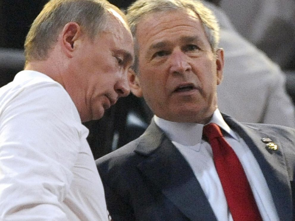 PHOTO: Russian Prime Mininster Vladimir Putin (L) talks with US President George W. Bush at the start of the opening ceremony of the 2008 Beijing Olympic Games in Beijing on August 8, 2008.